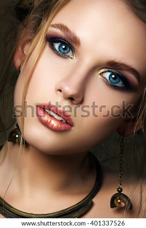 Close-up beauty portrait of funny girl with big blue eyes. Modern multicolored smokey eyes make-up. Studio shot. - stock photo