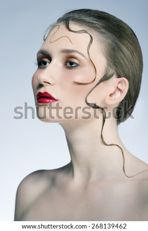 close-up beauty portrait of sensual woman with cute make-up, red lipstick and creative decorative hair-style  - stock photo