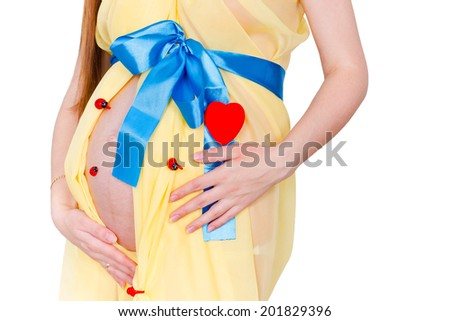 Close up belly of pregnant woman in the yellow fabric with a blue bow near the heart and ladybirds at white background - stock photo