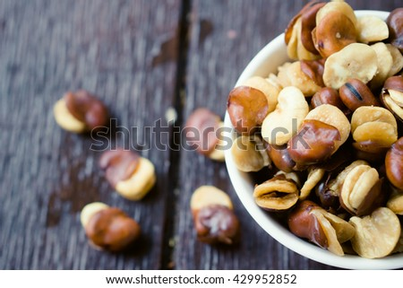 Close up belted broad bean in the white bowl on wooden background.Nuts Concept.Broad bean. - stock photo
