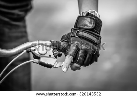 Close up bicycle rider's hands on a bicycle handlebar. black and white filter - stock photo