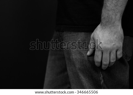 close up black and white image of a man wearing jeans and a black t shirt with his hand at his side standing in front of a black background