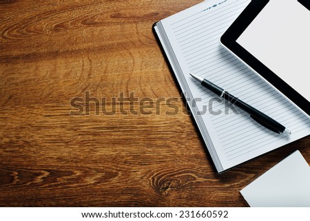 Close up Black and White Notes, Paper, Pen and Tablet Computer on Top Wooden Table with Copy Space on the Left Side for the Texts. - stock photo