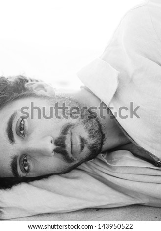 Close up black and white portrait of a young attractive man lying down and relaxing on a white sand beach with the sunset behind him with flare and flooding light, on vacation.