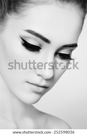 Close-up black and white portrait of young beautiful girl with cat eye make-up - stock photo