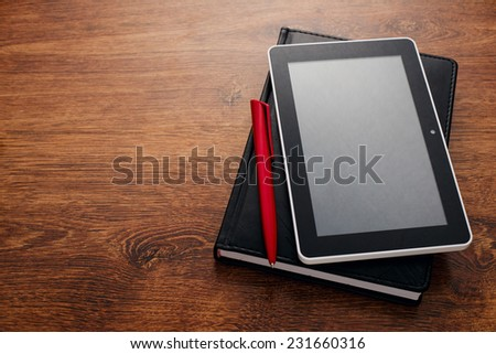 Close up Black Pen and Tablet Gadget on Top of Closed Black Book at the Wooden Table with Copy Space on the Left Side. - stock photo
