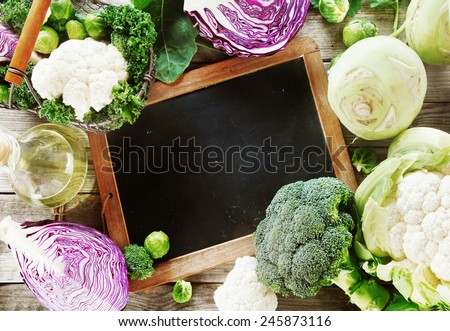 Close up Blank Black Board on Wooden table Surrounded by Healthy fresh Vegetables. Emphasizing Copy Space. - stock photo