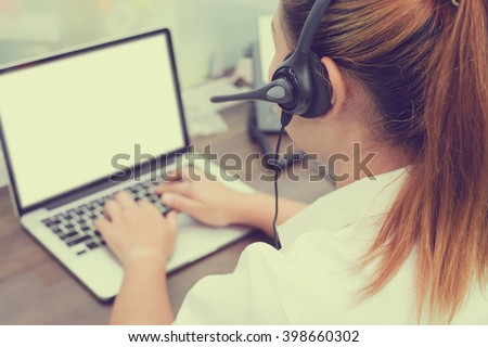 close up blur call center woman talking/working:focus on headphone asian girl answer customer's question or partner concept:people with technology and innovation:startup business.vintage filter effect - stock photo