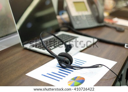 close up blurred of headset of call center hotline at computer office room:telemarketing business financial concept:headphone laptop telephone and statistics graph in image picture:telework corporate - stock photo