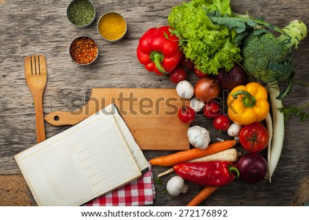 Close up board cooking wood more vegetable ingredients, and old notepad with recipes - stock photo