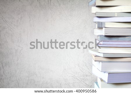 Close up book stacked  with the grunge concrete wall background - stock photo