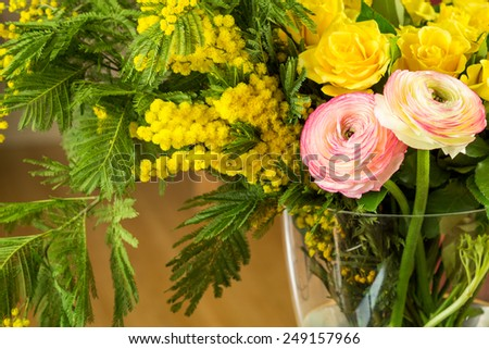 Close up Bouquet of Fresh Cut Beautiful Flowers, on Transparent Glass Vase with Water, on Top of the Table. - stock photo