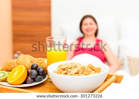 close-up breakfast on a tray and a portrait of the girl is not in focus - stock photo