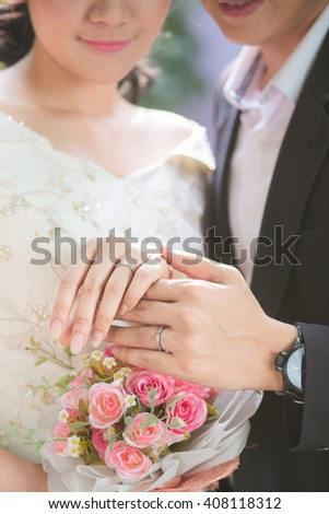 Close up bride and groom hand ware wedding ring - stock photo