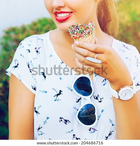 Close up bright image of woman with cone chocolate ice cream, wearing white vintage dress and heart sunglasses, have big smile and full red lips. - stock photo