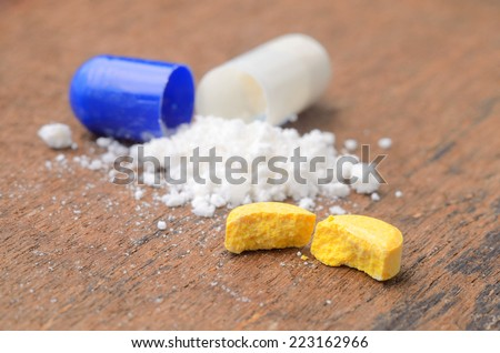 close up broken medicine tablet and opened medicine capsule pill with powder background