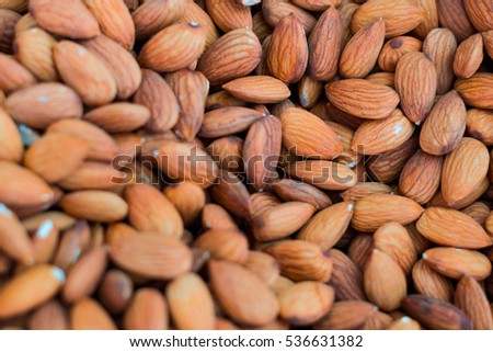 close up brown organic almonds nuts is healthy natural food,selective focus.