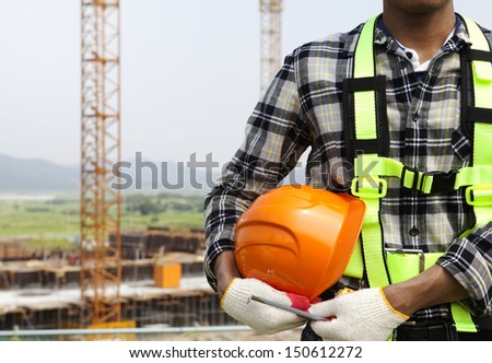 Close-up building construction worker holding helmet, construction safety concept - stock photo