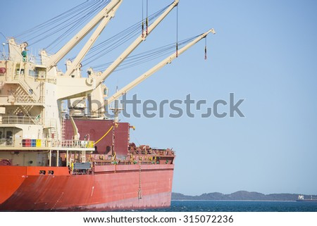 Close up Bulk carrier ship with cranes anchoring at loading terminal of port, with ocean water, coast at horizon, blue sky, copy space. - stock photo