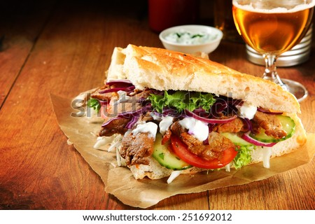 Close up Burger Slice with Grilled Meat Doner and Veggies on Brown Paper, Placed on Wooden Table. - stock photo