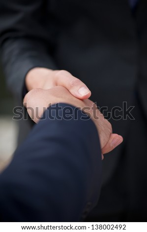 Close up business man and business woman handshake - stock photo