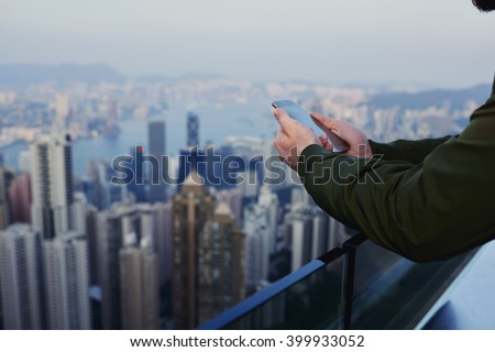 Close up business man is reading financial news in internet via cell telephone, while is standing on skyscraper building roof with view of developed China's business center background with copy space - stock photo