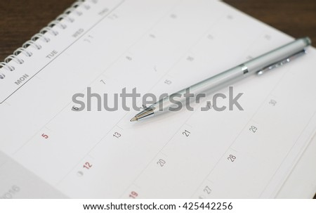 close up business pen lay on calendar schedule page paper for make important appointment:note meeting time:reminder or alert when event has occurred:avoid forgetting or miss something in the day idea - stock photo