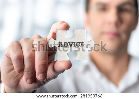 Close up Businessman Hand Holding Puzzle Piece Emphasizing Conceptual Advice Text. - stock photo