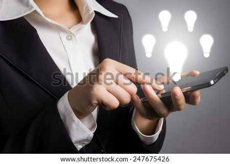 Close up businessman in black suit with hand touching smart phone and light bulb icon. - stock photo