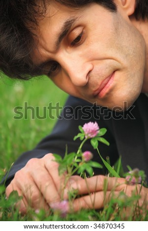 close-up businessman lying on grass looks at clover flower