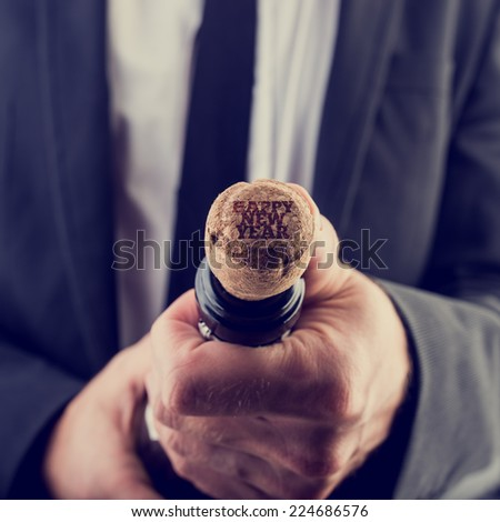 Close up Businessman Opening Wine Bottle with Happy New Year Texts on Bottle Cover. - stock photo
