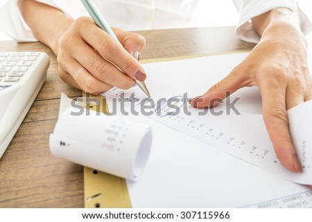 Close up Businesswoman Calculating Expenses on Printed Receipts at her Desk with Calculator on her Side. - stock photo