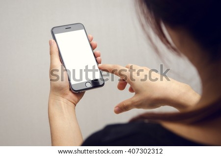 Close up Businesswoman hand holding and using smart phone with white blank empty screen. - stock photo