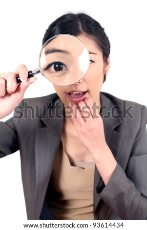 close-up businesswoman holding and looking at magnifying glass - stock photo