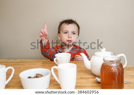 Close-up candid natural portrait of cute little boy toddler in kitchen drinking tea juice, making funny face, showing finger, lifestyle documentary style, grainy film effect - stock photo
