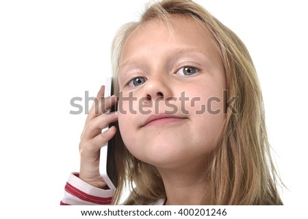 close up candid portrait of beautiful female child with blond hair and blue eyes using mobile phone talking happy and playful isolated on white background in children smartphone addiction concept - stock photo
