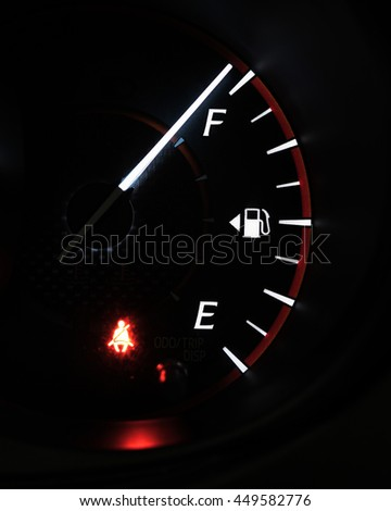 Close-up car dash board petrol meter, fuel gauge, on black background with over full gasoline in car or vehicle with red light of fasten seatbelt warning sign on . - stock photo