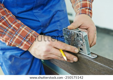 Close-up carpenter hands with doorlock during lock process installation into wood door - stock photo