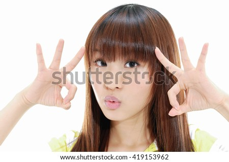 Close up casual young woman doing the ok sign on eye - stock photo