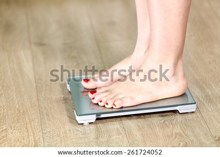 Close-up Caucasian legs standing on the floor scale - stock photo