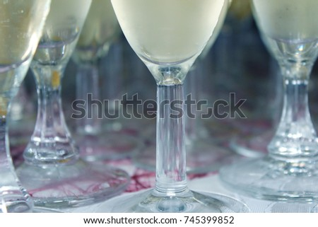 Close up champagne glasses, feet of glasses filled with champagne