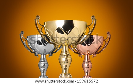 close up champion trophies on yellow background - stock photo