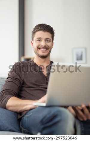 Close up Cheerful Handsome Young Guy Holding his Laptop Computer, Sitting on the Couch at the Living Room and Looking at the Camera. - stock photo
