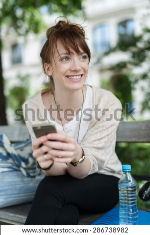 Close up Cheerful Pretty Girl Sitting at the Bench and Leaning her Body Forward, Holding her Mobile Phone While Looking Into Distance with a Toothy Smile. - stock photo