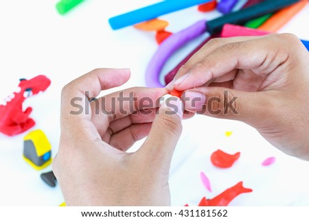Close up. Child playing and creating toys from play dough. Child molding model clay. Strengthen the imagination of child. - stock photo