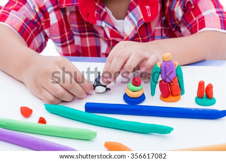 Close up child's hand creating toys from play dough. Strengthen the imagination of child. Child moulding whale modeling clay. - stock photo