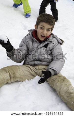 close up child sitting on the snow pulling snowball - stock photo