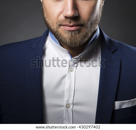 Close-up chin portrait of handsome stylish caucasian bearded young man in elegant blue suit and white shirt with perfect hair style. Toned - stock photo