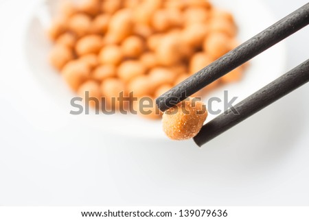 Close up chopstick holding a spicy peanut snack - stock photo