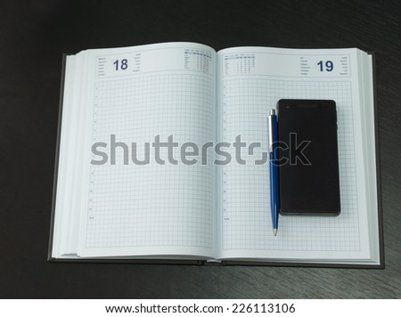 Close up Clean Open Memo Notebook with Blue Pen and Mobile Phone on Black Table - stock photo